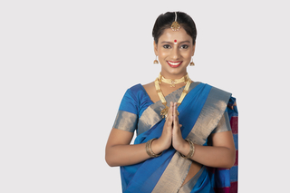 A beautiful south Indian woman is standing with a white background to welcome people - Namaste greeting gesture
