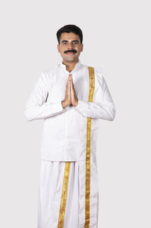 Portrait of a south Indian man standing to welcome people for a festival celebration, white background - Indian / Onam festival