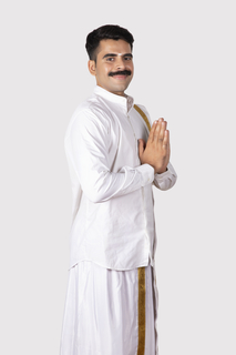Image of a young handsome south Indian man standing in greeting pose to welcome people - Onam / Indian festival