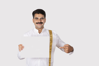 Excited south Indian man is holding a banner or placard and pointing towards it - white background