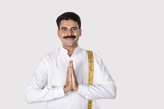 Portrait of a smiling south Indian man with white background standing in greeting pose - Onam / Indian festival
