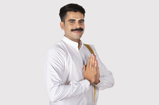 Portrait of a healthy south Indian man standing in greeting pose with white background - Onam festival