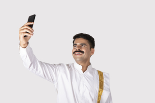 Portrait of a smiling south Indian man taking a selfie with his smartphone / mobile - technology concept