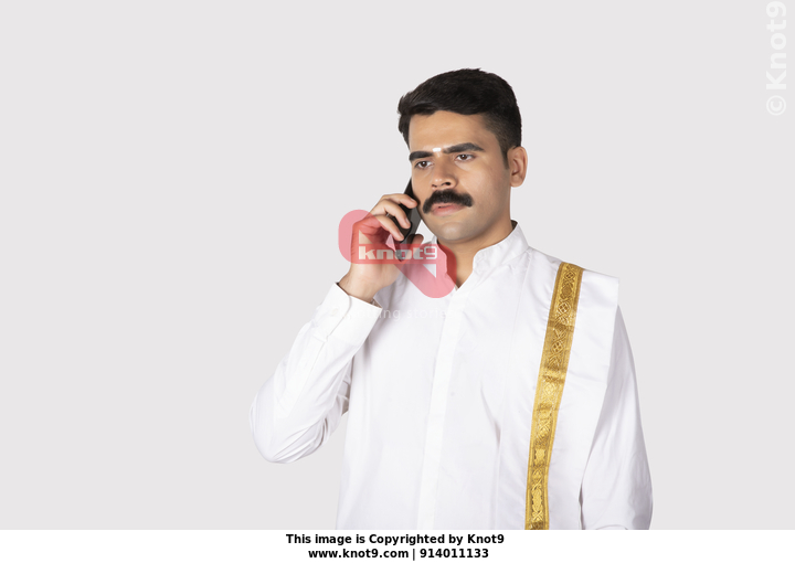 1a054a309d Portrait of a south Indian man looking serious while talking on a mobile /  smartphone with white background