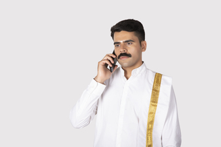 Portrait of a south Indian man looking serious while talking on a mobile / smartphone with white background