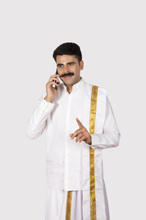 Young south Indian man standing with a white background and talking on mobile while making hand gesture