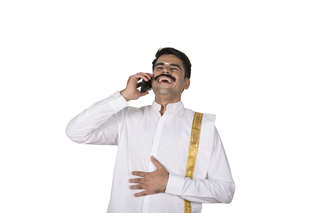 Portrait of a south Indian man talking on mobile and laughing loudly- white background image