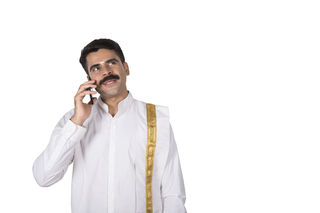 Happy south Indian man talking on smartphone/ mobile with white background- technology concept