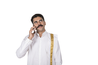 Young south Indian man wearing south outfit is talking on mobile / smartphone - white background