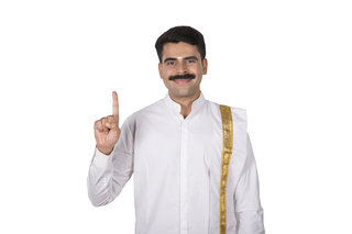 Portrait of a young south Indian man making a gesture showing / pointing one finger with white background