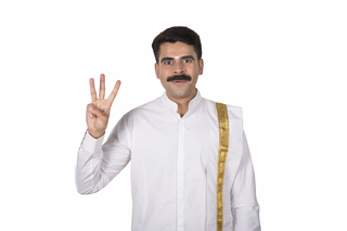 Portrait of a young south Indian man showing up three finger gesture on white background