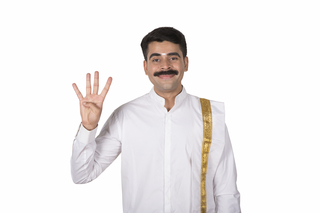 Portrait of a happy south Indian man in traditional dress showing four fingers - white background
