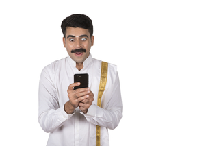 A happy south Indian man holding smartphone / mobile phone - showing excitement and surprise. Technology concept