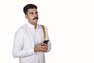 South Indian Man holding a mobile phone -  wearing a southern dress with gamachha / hand towel. White background