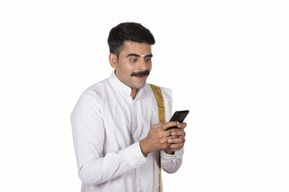 Happy South Indian Man holding a smartphone, isolated on white background - Technology Image concept