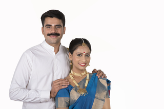 Stock Photo - Portrait of a traditional South Indian couple in traditional dress on white background