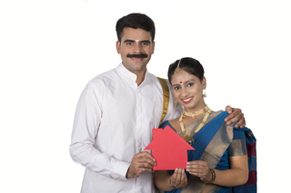 Close up image of a South Indian couple showing at a model home - Finance, Home Loan, Banking concept