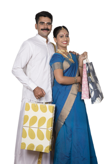 Newly wed south Indian couple standing together holding shopping bags - White background