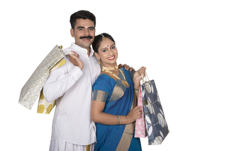 A south Indian couple wearing a traditional dress is holding gift bags after festival shopping