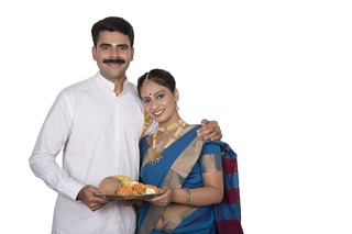 Smiling south Indian couple standing together with a white background and holding a thali/tray to offer prayer