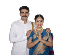 Beautiful south Indian couple in a traditional dress standing  together in greeting pose with white background - Onam festival