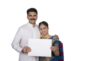d275005670 Portrait of a smart south Indian couple holding a placard in front of white  background -
