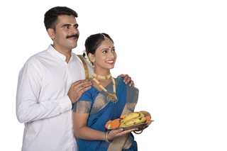 Portrait of a healthy south Indian couple going to temple to pray on Onam festival - Looking sideways on white background