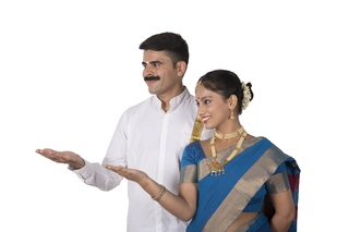 Attractive south Indian couple in ethnic / traditional dress presenting a product - Looking sideways on white background