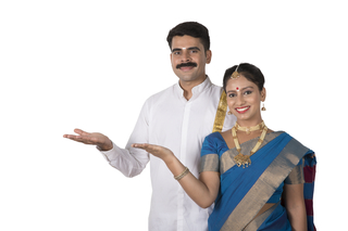 Young south Indian couple standing together with white background holding a product in hand