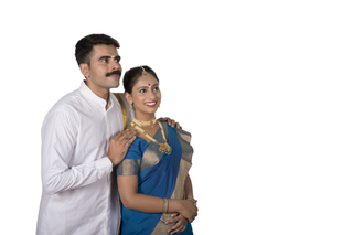 Portrait of a beautiful south Indian couple standing together with white background - Looking sideways