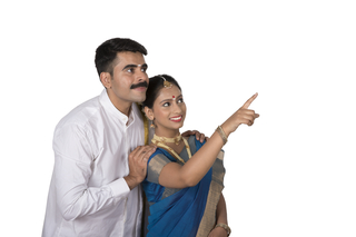 Portrait of a happy south Indian couple with white background - Pointing away