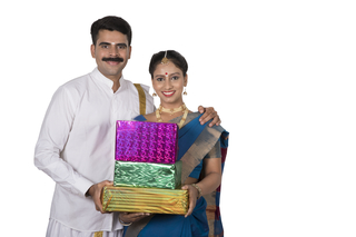 5c554a2353 Portrait of a south Indian couple with white background holding gift boxes  purchased during festival shopping