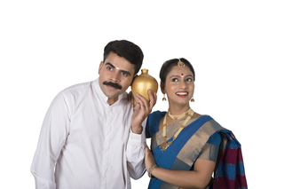 Beautiful young couple standing with white background - shaking their piggy bank and checking coins (money)