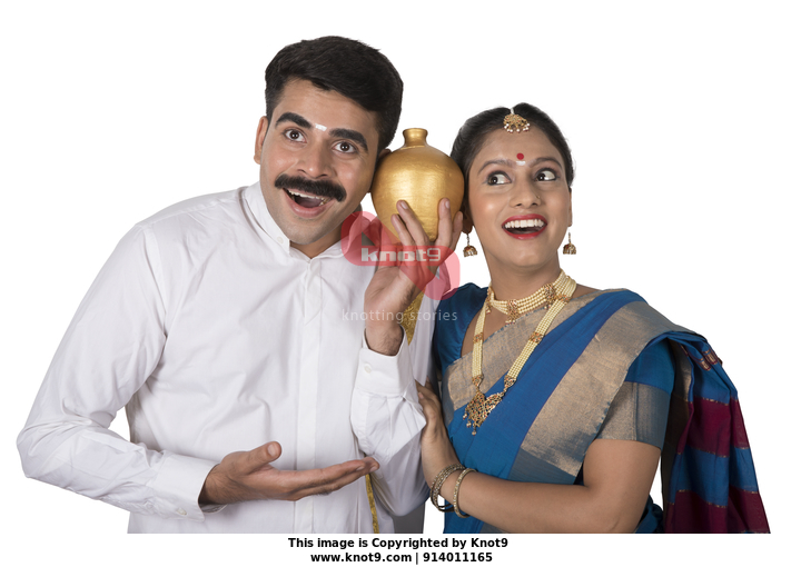 19e2992310 Portrait of a south Indian couple standing together with white background  holding piggy bank