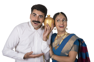 Portrait of a south Indian couple standing together with white background holding piggy bank