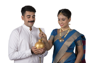 Portrait of a smart south Indian couple standing together with white background -  holding a piggy bank and woman putting the coin (money) in it