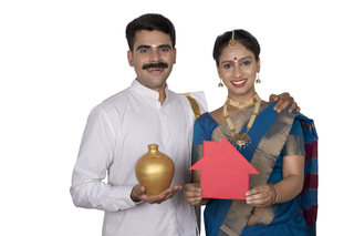Happy south Indian couple standing together holding piggy bank and house replica with white background