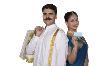 Smart south Indian couple shopping for Onam celebration, wearing traditional clothes
