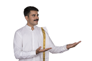 Handsome south Indian man in traditional outfit showing a product