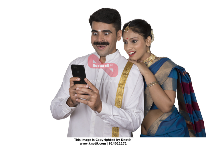 e1a75ea19e Excited couple (husband and wife) checking amazing offers during festival  time in their smartphone: Onam festival