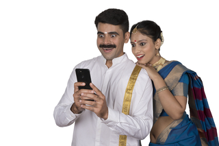 Excited couple (husband and wife) checking amazing offers during festival time in their smartphone: Onam festival