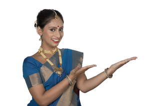 Smart South Indian woman in traditional dress - standing and pointing towards white background