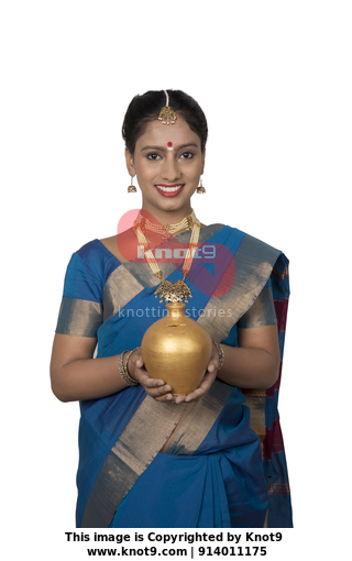 542ddc083e South Indian woman wearing silk saree is holding a piggy bank - saving  money, finance concept (White background)
