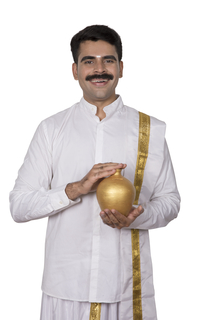 Happy south Indian man holding piggy bank facing towards the camera - money saving concept (White Background)