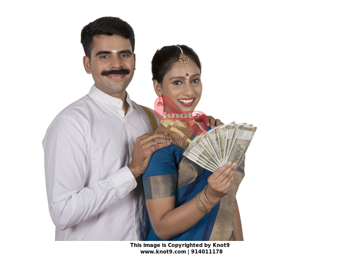 d9f6d6df2a Happy south Indian couple flashing Indian currency - Onam celebration.  White background