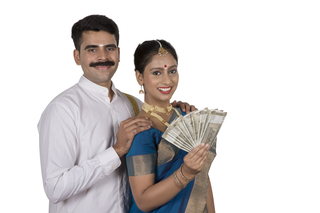 Happy south Indian couple flashing Indian currency - Onam celebration. White background