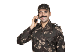 Cheerful army officer talking on mobile phone wearing his uniform