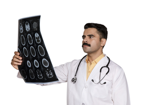 A serious and young Indian doctor examining his patient's MRI / X-ray reports