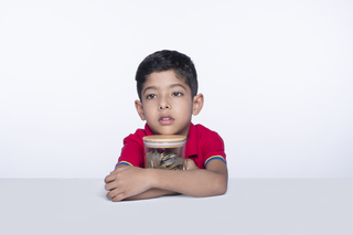 Portrait of a little young boy holding glass jar full of coins against the white background