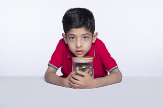 Little child boy holding jar full of coins posing towards the camera - savings concept